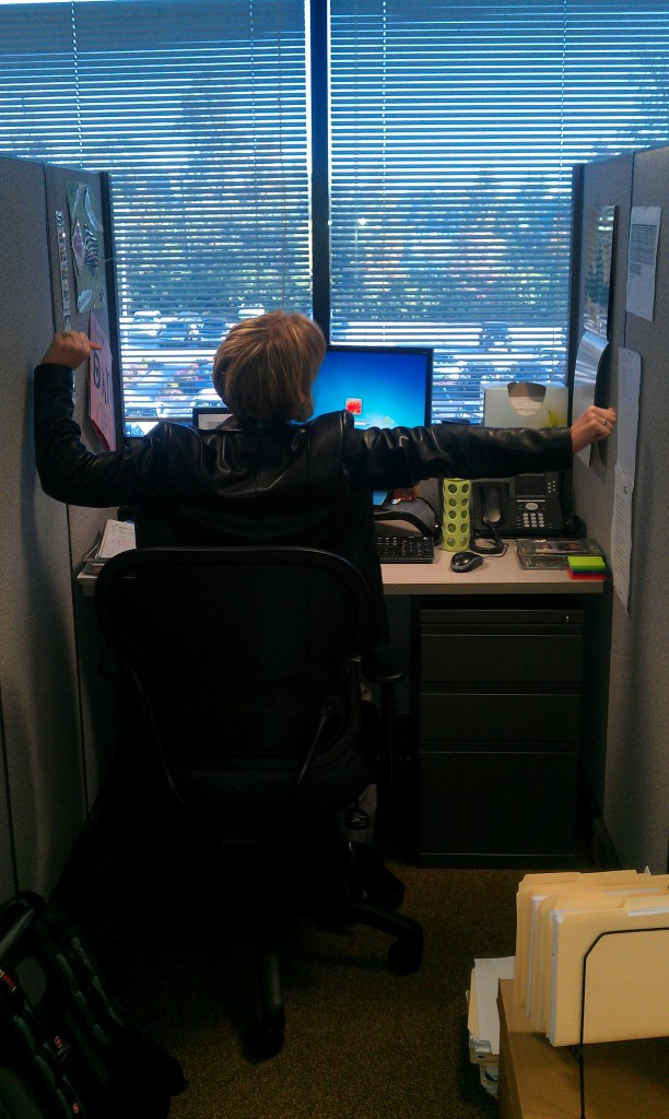 Michelle tries to stretch her arms in her new cube